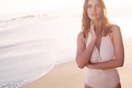 model on the beach wearing swim suit