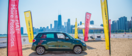 fiat car on sand next to the water
