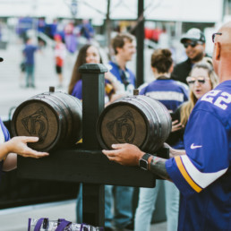 viking fans lifting up barrels of whiskey