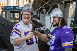 vikings fan celebrate in front of highland park's boat