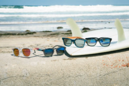 glasses on top of surfboard next to waves