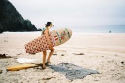 surfer walking next to mayde towel