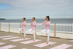 3 ladies doing the same yoga pose together next to the water