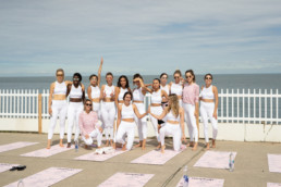 a group of girls taking a picture together next to yoga mats